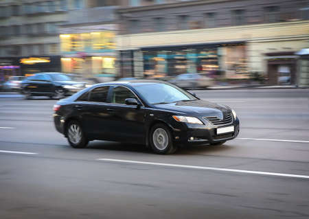 sedan: black luxury car moves on the city street