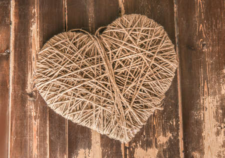 skein: heart symbol wound with rope on wooden background