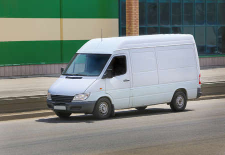 delivery van: white van on the street before the building