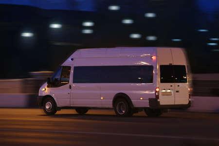 белый микроавтобус движется на улице города в ночное время