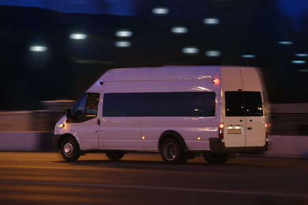 white minibus moves on the city street at night