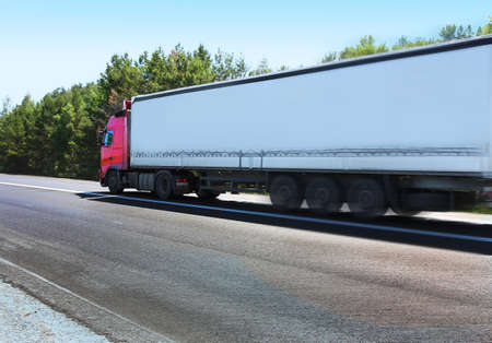 trailer with red awning moves at high speed on the highway