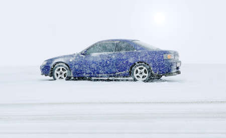 blue car in the winter on snow under snowfall Stock Photo