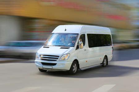 white minibus goes on the city street Standard-Bild