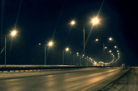 winter road: winter highway at night shined with lamps Stock Photo
