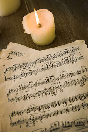 music notes on old paper and candles on table photo