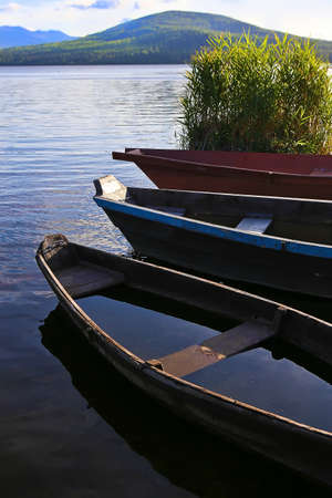 old wooden boats on mountain lake photo