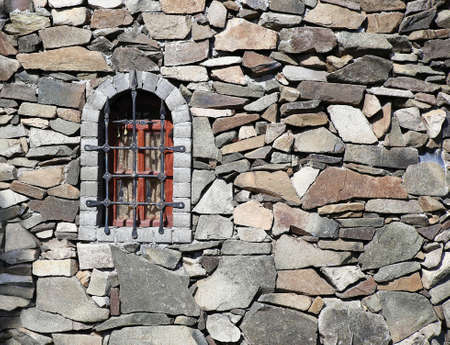 stone wall of fortress with window and lattice photo