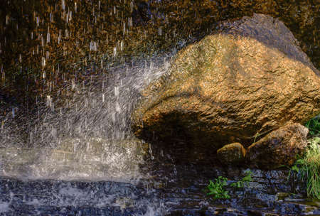 shined: water drops falling on  stone shined with sun Stock Photo