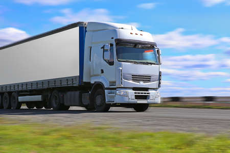 white truck transports freight on the country highway photo