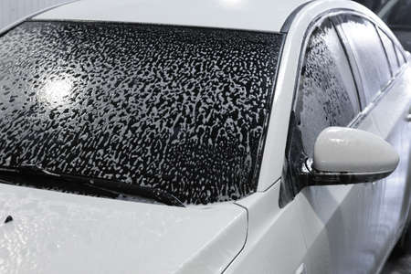 white modern car covered with foam in car wash photo