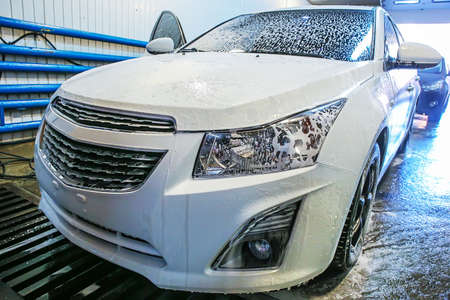 bubble car: white modern car covered with foam in car wash