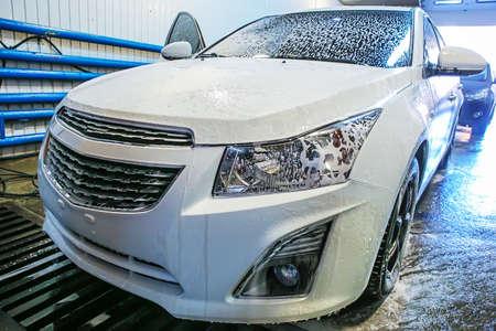 witte moderne auto bedekt met schuim in carwash