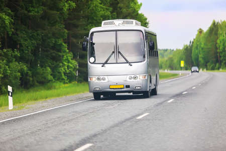 silvery bus goes on the country highway photo