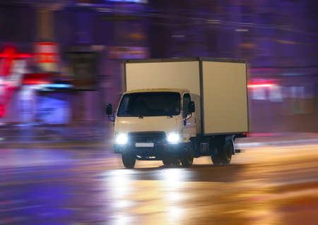 грузовик движется в дождь по ночному городу