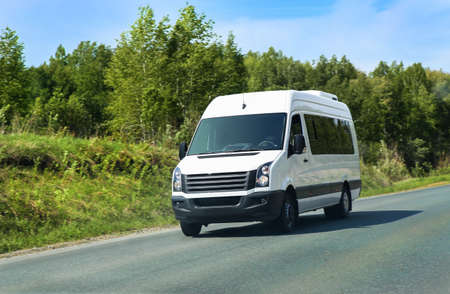 minibus: minibus goes on the country highway along the wood