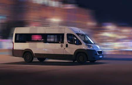 夜の街に移動する白いミニバス