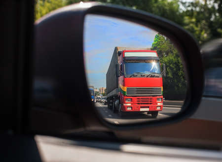 behind scenes: red truck reflection in a car mirror Stock Photo