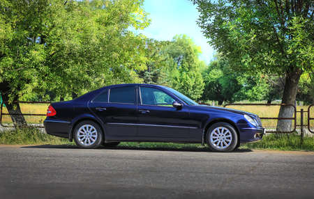 dark car on roadside near park Stockfoto