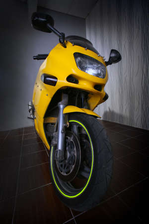 yellow sports motorcycle indoors frontally photo