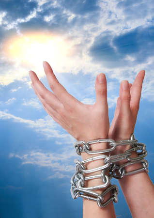 lifted hands: female hands tied by chain lifted to sun