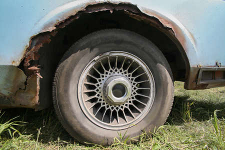 hubcap: old car with rust on body close up