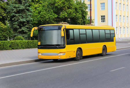 tourist feature: yellow bus goes on the city street