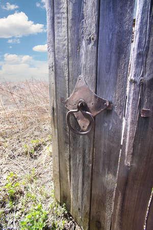 barn door: old wooden open door behind it field and sky