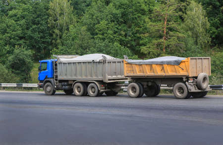dump truck: dump truck with  trailer moves on highway in country