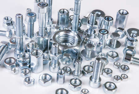 chromeplated bolts and nuts on white background