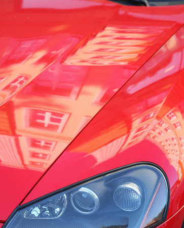 cowl: reflections of buildings on cowl of red car