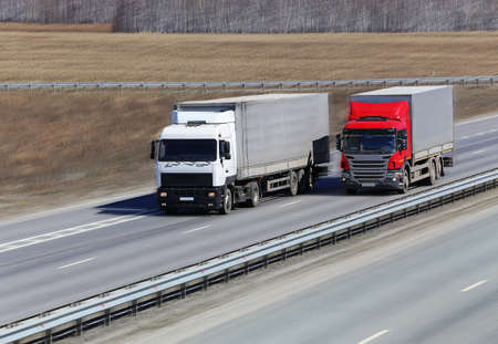 two trucks with containers move on highway