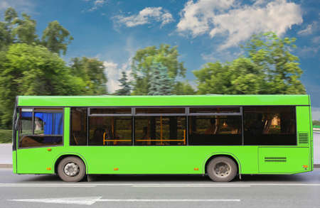 green city bus moves down the street against trees