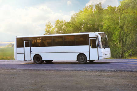 landscape mode: white bus goes on country highway in sunny day Stock Photo
