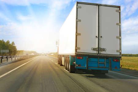 trailer: cami�n grande va en la carretera a la salida del sol Foto de archivo