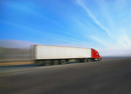 fast shipping: trailer with red awning moves at high speed on the highway Stock Photo