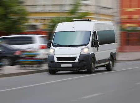white minibus goes on the city street Foto de archivo