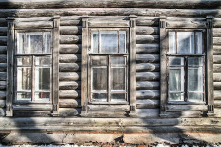 wall of old log house with windows photo