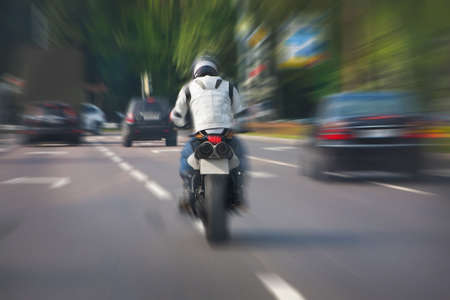 city road: motorcycle quickly moves on the city road Stock Photo