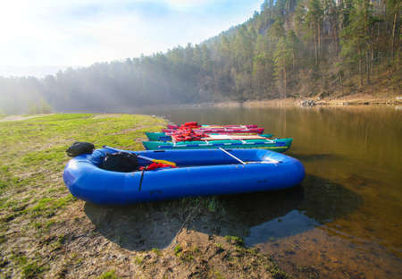 rafting: catamarans and rubber boat on river bank Ai Ural Russia