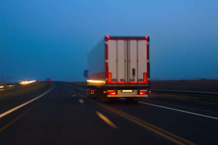 multiple lane highway: truck moves on country highway at night Stock Photo