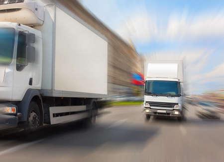 zwei Lastwagen fahren auf Stadtstraße in sonnigen Tag