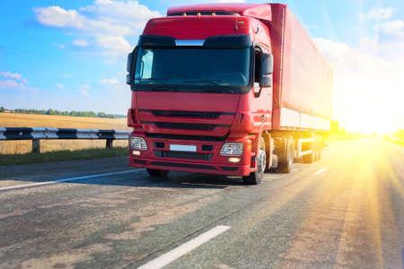 remolque: camión rojo en carretera del país en la puesta del sol
