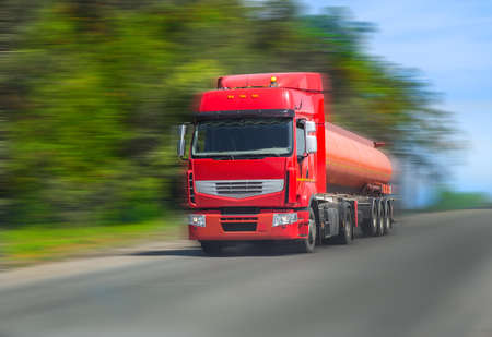 multiple lane highway: red fuel truck transports fuel to country highway