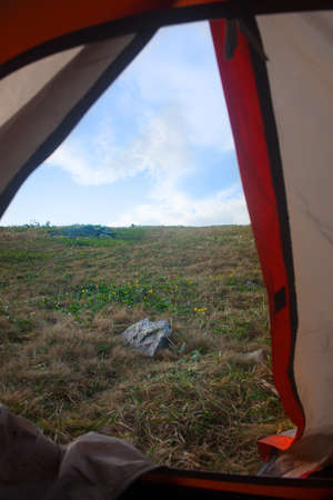 extreme angle: view of landscape from doors of open tent Stock Photo