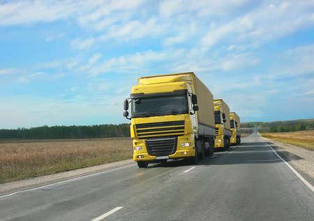 escort: escort of yellow trucks on country road