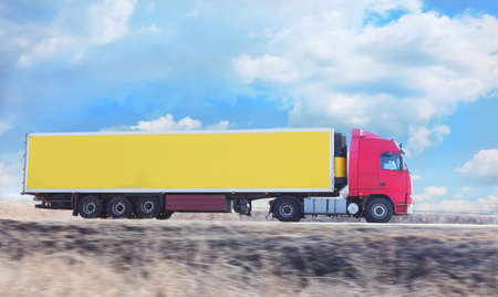 fast shipping: red truck with yellow container goes on highway Stock Photo