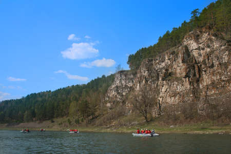 tourism russia: tourists on catamarans float down the river against mountains Stock Photo