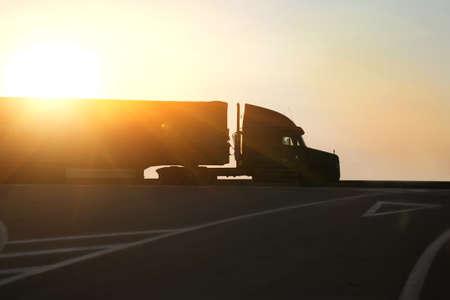 грузовик идет по шоссе в вечернее время на закате Фото со стока