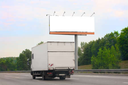loading truck: white truck goes on highway by billboard Stock Photo